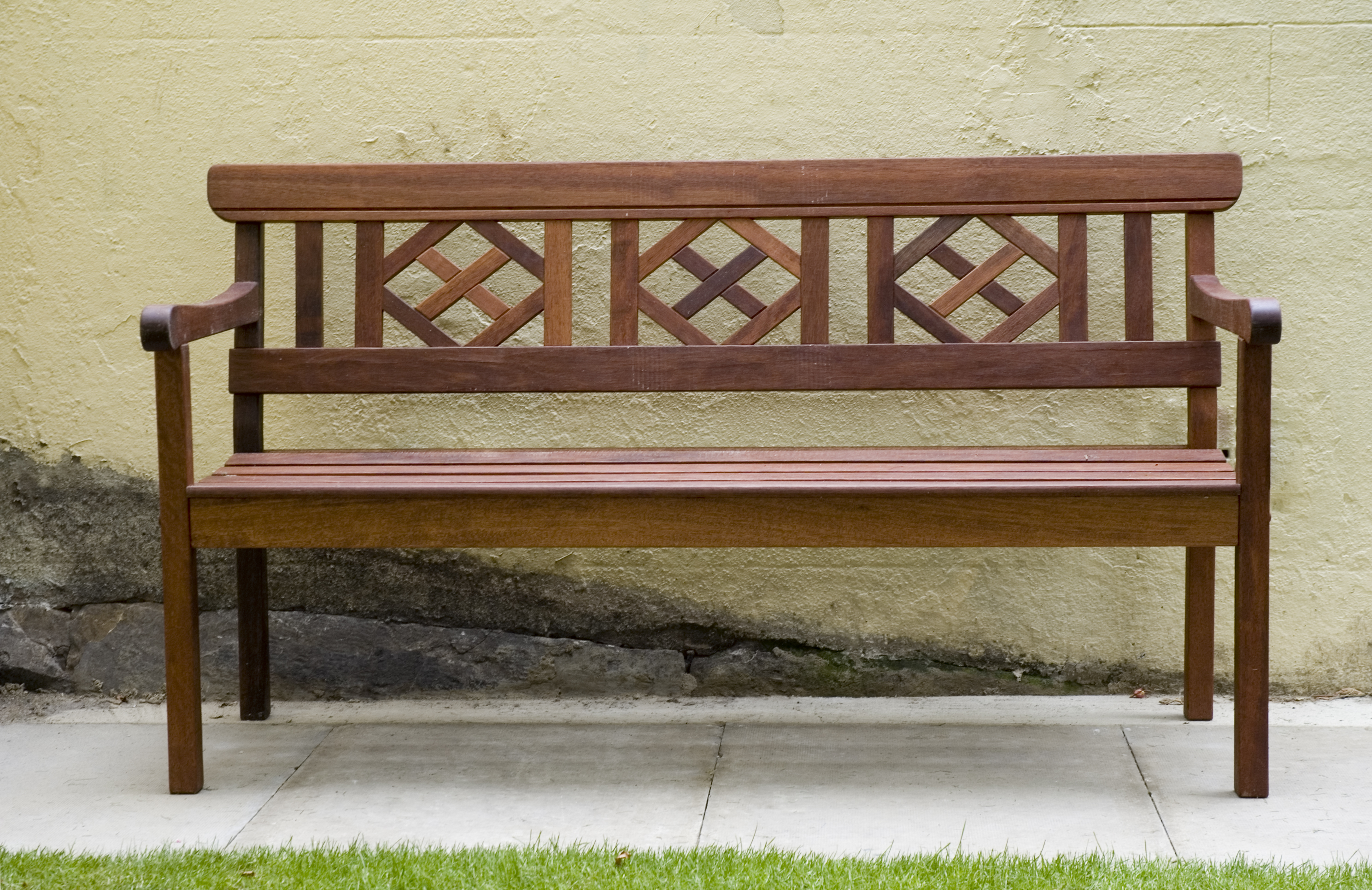 Wooden Park bench against textured yellow wall